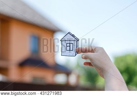 Woman Holding A Drawing Of A House In Front Of A Blurred Cottage. Woman's Hand Showing A Paper Figur