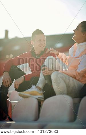 Smiling woman jogger in sportswear sitting on tribune talking with young runner man