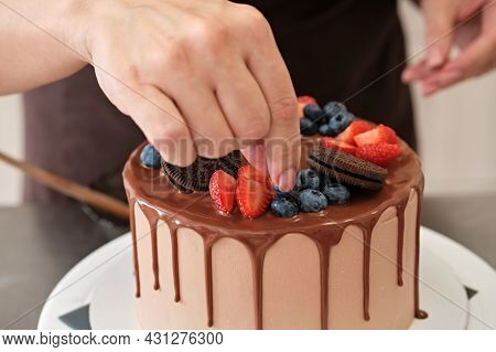 Woman Pastry Chef Decorates Chocolate Cake With Berries And Cookies, Close-up. Cake Making Process,