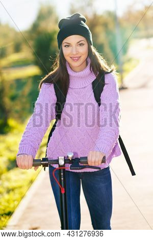 Young Woman In Her Twenties Riding An Electric Scooter.