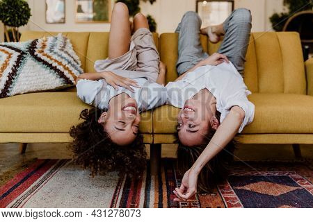 Cheerful women lying upside down on a mustard yellow couch