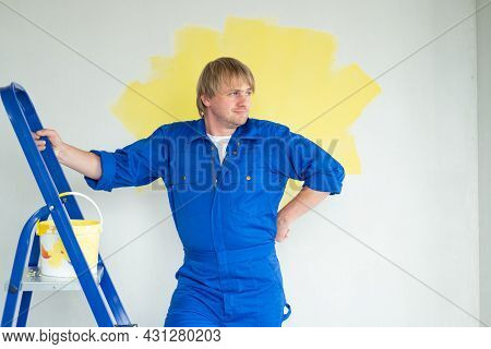 Tired Man Painting Wall In Yellow Color With Roller. Renovation, Repair And Redecoration Concept