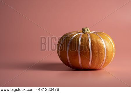 Pumpkins On Pastel Pink Background With Pastel Ribbon. Autumn, Fall, Halloween Concept.