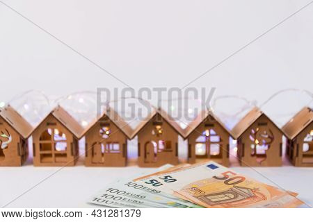 In A Row There Are Cute Wooden Houses, New Years Garlands. In The Foreground Are Eu Banknotes. Home