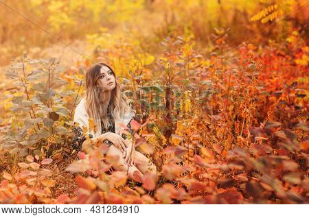 Beautiful Young Blonde Woman Wearing Boho Style Long Dress While Sitting With Pensive Look In Tall G