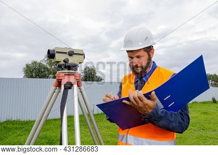 A Civil Engineer Writes Down The Readings Of The Optical Level On A Piece Of Paper In A Folder. A Ma