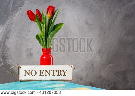 A Sign Prohibiting Visiting The Room By A Red Vase On The Table. Decorative Ceramic Vase With Red Fl