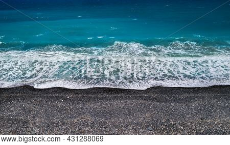 Sea Shore Background With Black Sand And Pebbles And Breaking Wave, High Angle Perspective