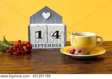 Calendar For September 14 : The Name Of The Month In English, Cubes With The Number 14, A Yellow Cup