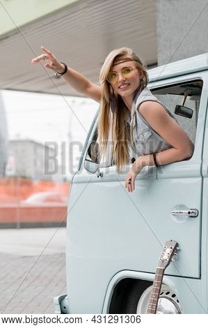 A Beautiful Young Hippie Woman In Yellow Sunglasses Looks Out The Window Of A Blue Vintage Minivan.
