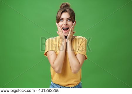 Indoor Shot Of Excited And Surprised Energized Attractive Glamorous Female In Yellow T-shirt Touchin
