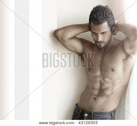 Beautiful muscular male model with nice abs in jeans near window with copy space