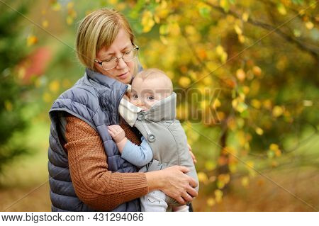 Grandmother With Her Infant Grandson In A Baby Carrier Having Fun Hiking In A Forest On Beautiful Au