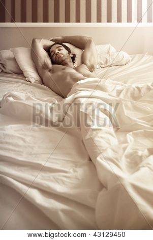 Sensual portrait of a gorgeous sexy nude male model laying in bed
