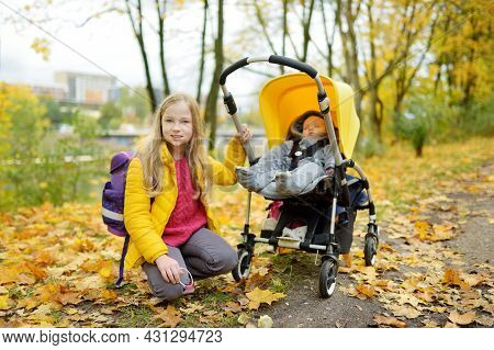 Cute Big Sister Walking In A Park With Baby Brother In Pushchair. Siblings Walk In City Park. Girl P