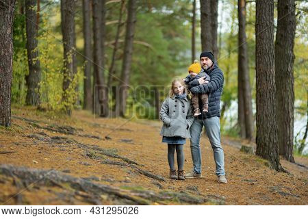 Father And Two Children Having Fun On Late Autumn Day By The Lake. Adorable Baby Boy Being Held By H