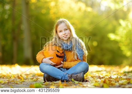 Cute Young Girl Holding A Small Pumpkin With Painted Scary Face On Sunny Autumn Day. Kid Trick Or Tr