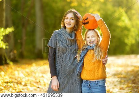 Two Cute Young Girls Holding A Small Pumpkin With Painted Scary Face On Sunny Autumn Day. Kid Trick