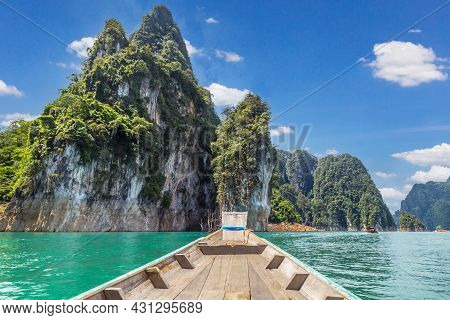 Wooden Thai Traditional Long-tail Boat On A Lake With Mountains At Ratchaprapha Dam Or Khao Sok Nati