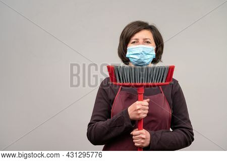 A Woman In A Surgical Mask, A Middle-aged European, A Cleaner, Holds A Mop In Her Hands. The Concept