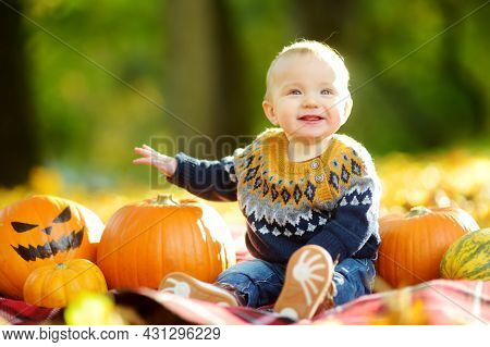 Cute Small Baby Boy Sitting Near Small Pumpkin With Painted Scary Face On Sunny Autumn Day. Kid Tric