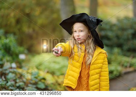 Cute Young Girl Wearing Black Witch Hat Having Fun With Magic Wand Outdoors. Kid Trick Or Treating O