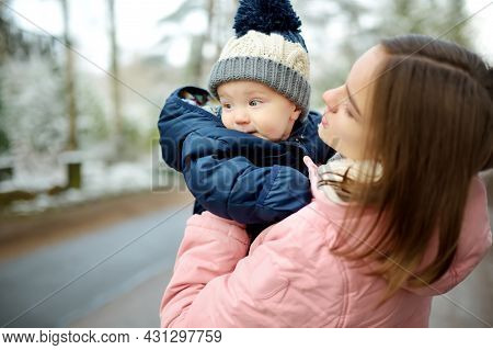 Big Sister And Her Baby Brother Having Fun Outdoors. Young Girl Holding Her Baby Boy Sibling On Wint