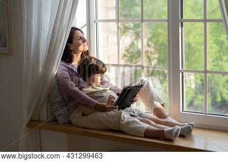Caring Mom Engaging With Small Preschool Son On Weekend Relaxed Sitting On Windowsill Hugging Kid Pl