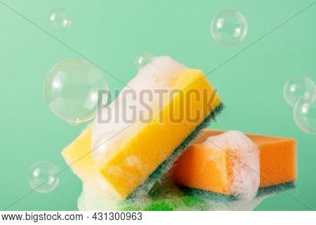 Colored Cleaning Sponges With Bubbles And Soapy Foam On Green Background. Wet Kitchen Dishwashing Sp