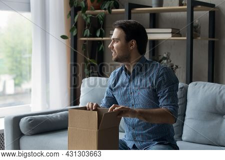 Happy Excited Millennial Guy Unpacking Carton Box At Home