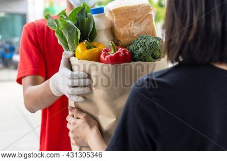 Asian Deliver Man Wearing Protection Face Mask Delivering Fresh Food Set Bag To Woman Customer At Do