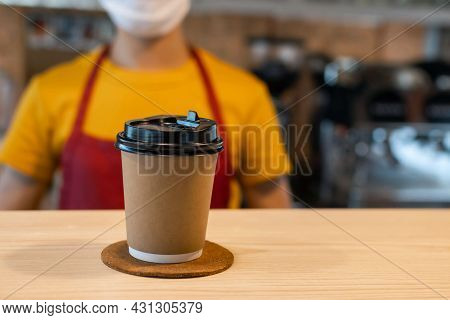 Hot Black Coffee Cup On Counter With Staff Woman Wearing Protection Face Mask On Background In Cafe