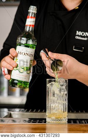 Ukraine, Kyiv - March 11, 2021: Bartender Pours Delicious Cucumber Syrup From Jigger Into Crystal Gl