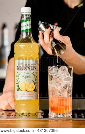 Ukraine, Kyiv - March 11, 2021: Lemon Rantcho Syrup Bottle On Bar And Crystal Glass Of Ice Cubes Int