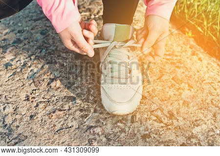 Top View Of Female Hands Tying Shoelaces On Jogging Sports Shoes, Closeup