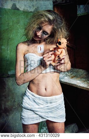 Strange Mad Girl With Creepy Ugly Doll In Forsaken Place (asylum). Crazy Young Woman (freak) Dressed