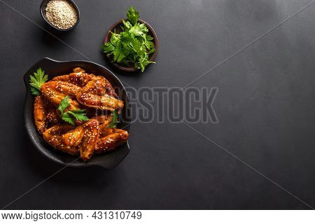 Teriyaki Chicken Wings With Sesame And Greens On Black Background, Top View, Copy Space. Asian Style