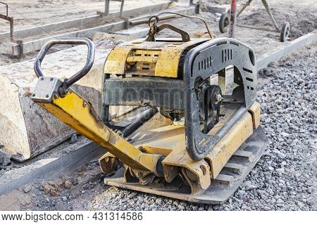 Vibratory Rammer With Vibrating Plate On A Construction Site. Compaction Of The Soil Before Laying P