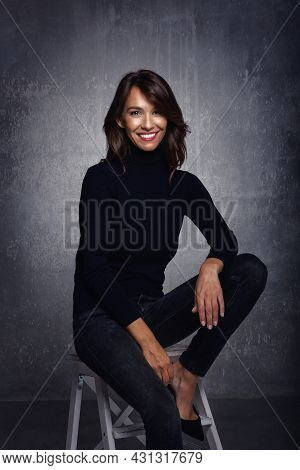 Beautiful Smiling Woman With White Teeth Sitting At Isolated Grey Background. Happy Woman Wearing Tu