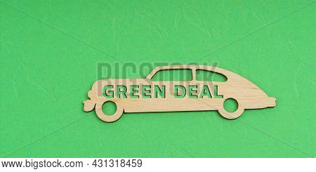 Ecology And Transportation Concept. On A Green Background, A Wooden Car With The Inscription - Green