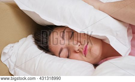 Irritated Woman Wearing Pink Pajama Lies In Bed Closing Ear With Hand And Large White Pillow Against