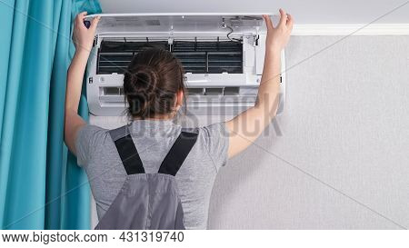 Brunette Woman In Workwear Opens White Ceiling Air Conditioner Unit Lid On Wall In Apartment Room Wi