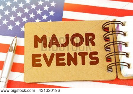 Politics And People Concept. On The Us Flag Lies A Notebook With The Inscription - Major Events
