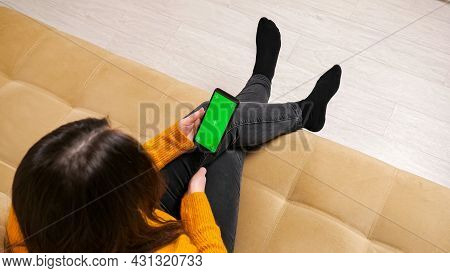 Long Haired Brunette In Jeans And Pullover Sits On Sofa Of Brown Colour And Types On Smartphone With