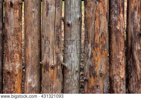 Wooden Fence Made Of Round Tree Trunks. Old Wooden Logs As Background Texture