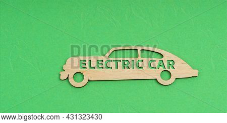 Ecology And Transportation Concept. On A Green Background, A Wooden Car With The Inscription - Elect