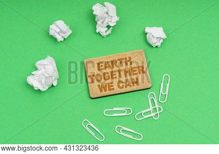 Ecology Concept. On A Green Background, Crumpled Paper, Paper Clips And A Sign With The Inscription