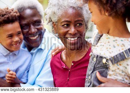Loving Grandparents Talking With Grandchildren In Garden At Home
