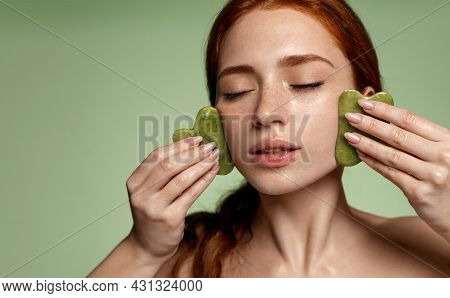 Guasha Face Massage With Jade Stone. Young Redhead Woman With Freckles, Massaging Facial Skin With G