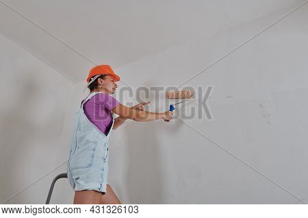 He Is Painting The Wall On A Metal Step-ladder